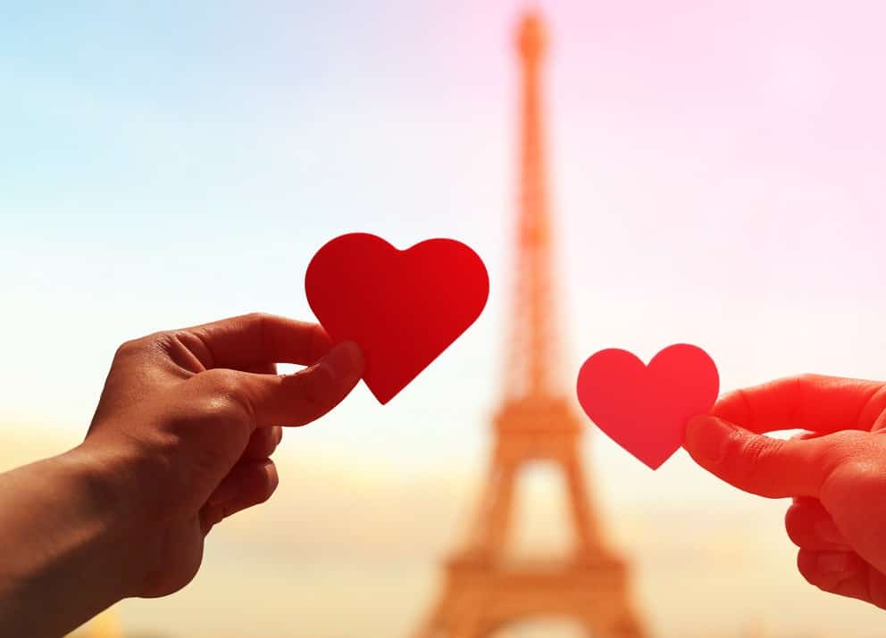 hands holding hearts in front of the eiffel tower