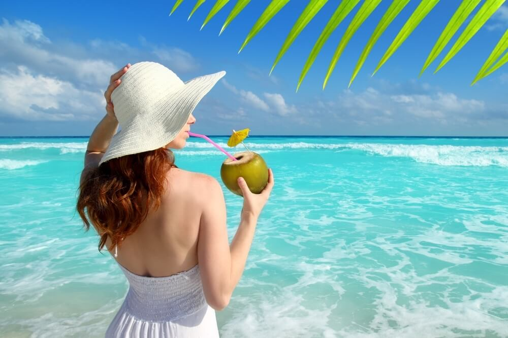 woman drinking coconut on a turquoise tropical beach