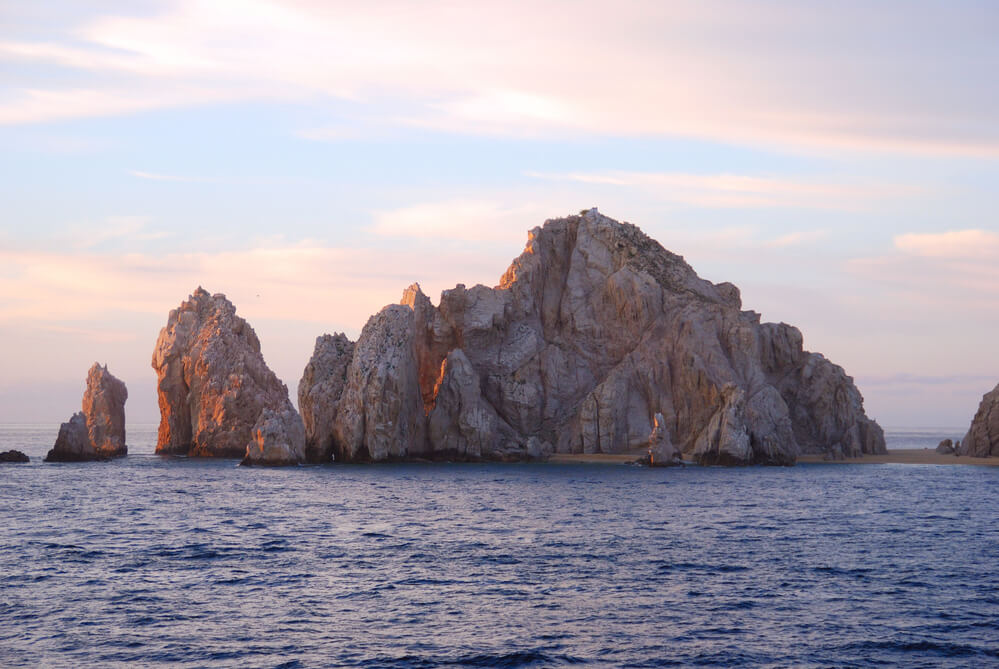 rocks on the water in los cabos at a pink sunset