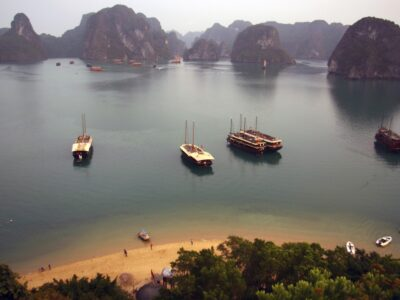 quiet beach in halong bay with karst formations behind