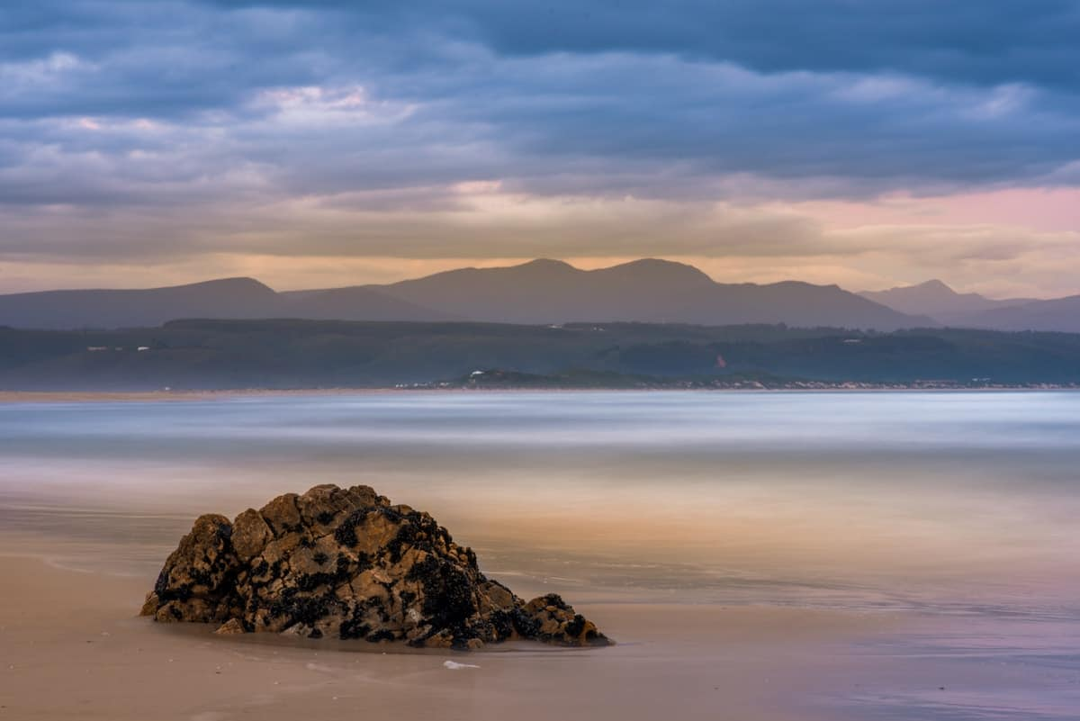 pastel beach shot of plettenberg bay with big boulder