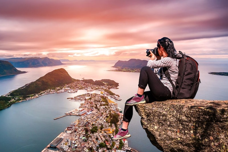 girl with backpack sitting on a cliff