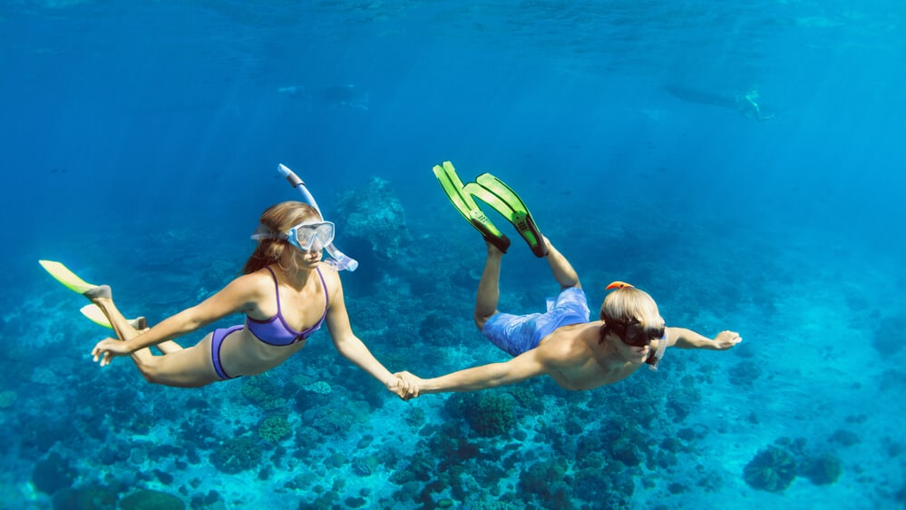 young couple snorkelling in the blue Caribbean sea