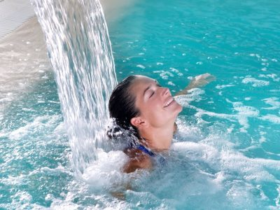 woman in pool with hydrotherapy waterfall jet