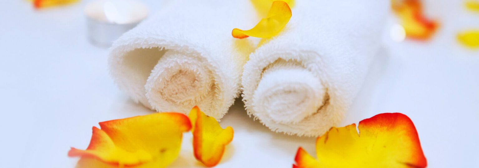 white rolled towels and orange blossoms at a spa